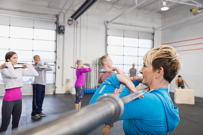 Group practicing clean lifts with barbells - p1192m1044124f by Hero Images