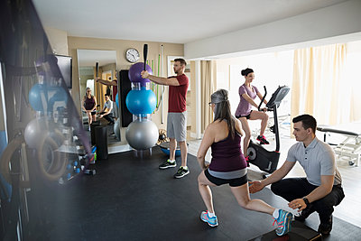 Male physiotherapist guiding clients stretching and exercising in clinic gym - p1192m1447353 by Hero Images