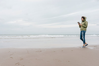 Woman walking on the beach with tablet - p300m1499498 by Kniel Synnatzschke