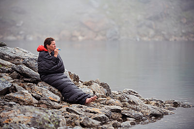 Woman in sleeping bag at lake - p312m2139178 by Hans Berggren