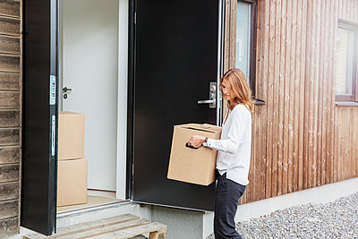 Woman carrying cardboard box into house - p352m2119229 by Helena Bonnevier