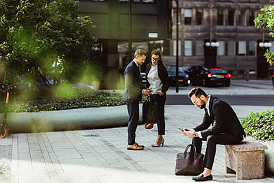 Businessman showing smart phone to female colleague while male coworker surfing net outdoors - p426m2169616 by Maskot
