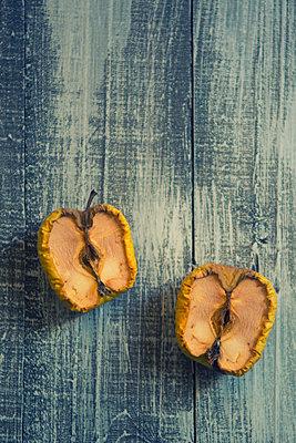 Alte Äpfel, halbiert auf einem Tisch - p794m2031128 von Mohamad Itani