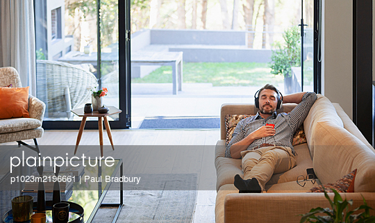 Man relaxing on living room sofa, listening to music with headphones and mp3 player - p1023m2196661 by Paul Bradbury