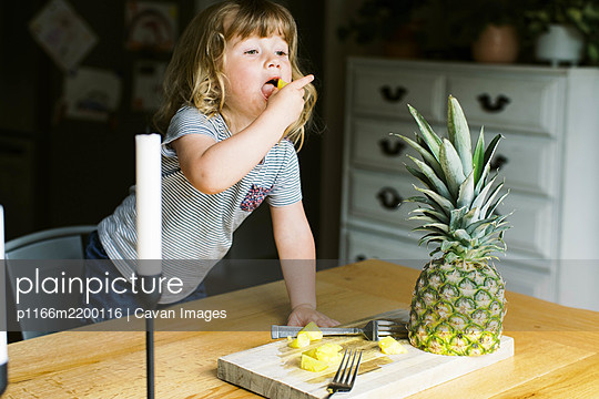 A little toddler girl having a healthy pineapple snack - p1166m2200116 by Cavan Images