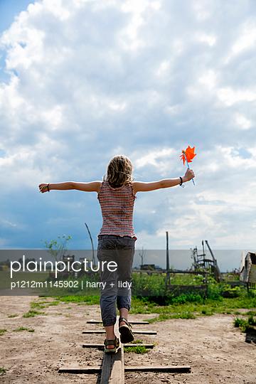 Mädchen balanciert - Rückansicht - p1212m1145902 von harry + lidy