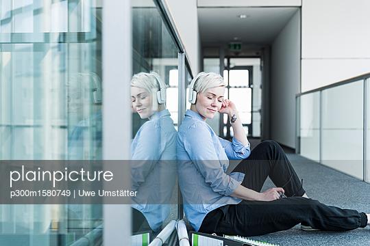 plainpicture - plainpicture p300m1580749 - Woman sitting on office flo... - plainpicture/Westend61/Uwe Umstätter