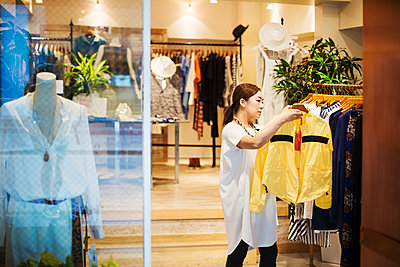 Woman working in a fashion boutique in Tokyo, Japan. - p1100m1185828 by Mint Images