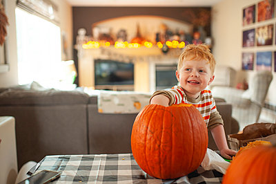 Toddler boy 3-4 years old scoops out pumpkin seeds with his hand - p1166m2236831 by Cavan Images