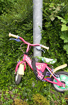 Small Childrens's bike attached to lamp post with a thick chain lock - p1231m1041961 by Iris Loonen