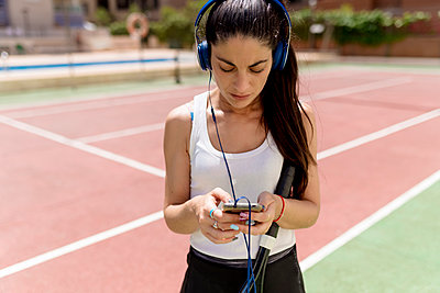 Female tennis player using smart phone while listening music in court on sunny day - p300m2213978 by Ezequiel Giménez