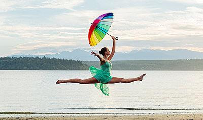 Caucasian ballerina jumping with multicolor umbrella on beach - p555m1232003 by Pete Saloutos