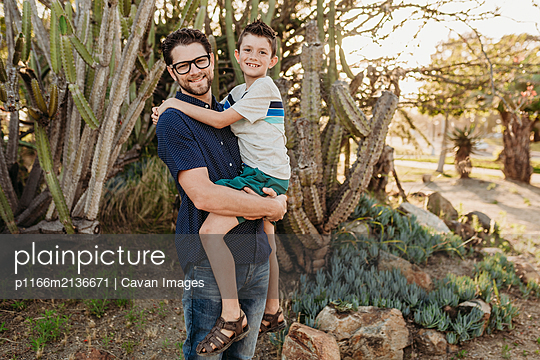 Portrait of father holding older son and smiling at the camera - p1166m2136671 by Cavan Images