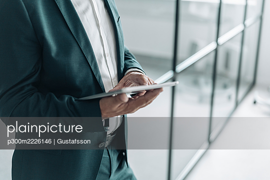 Businessman holding digital tablet while standing at office - p300m2226146 by Gustafsson