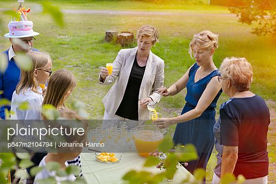Multi-generation Family Drinking Juice In Garden, Sweden    - p847m2104794 by Johanna Hanno