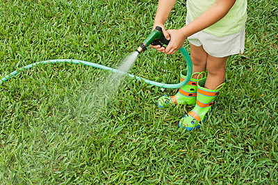 Girl watering lawn with garden hose, cropped - p624m710827f by Michele Constantini