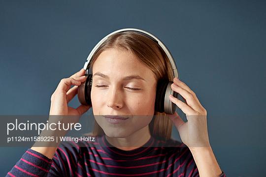 Junge Frau hört Musik über Kopfhörer - p1124m1589225 von Willing-Holtz