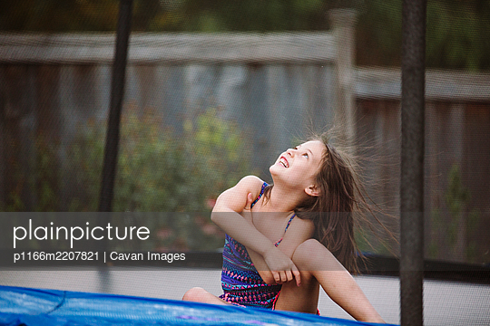 A laughing child with wild hair plays in a trampoline in her yard - p1166m2207821 by Cavan Images
