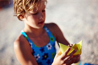 Mädchen am Strand bastelt ein Boot aus Papier - p1026m834447 by Secen-Steets