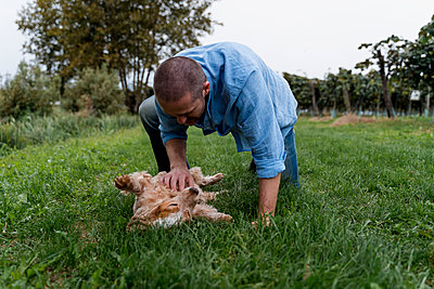 Man playing with his dog on a meadow - p300m2160214 von Mauro Grigollo