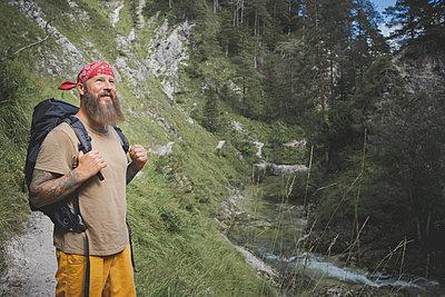 Bearded man wearing bandana standing in forest, Otschergraben, Austria - p300m2220973 by Epiximages