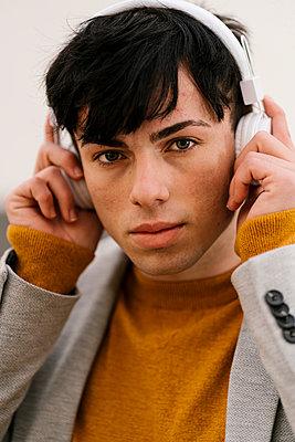 Young man adjusting headphones while standing outdoors - p300m2251039 by Ezequiel Giménez