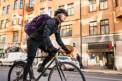 Woman riding bike in city - p312m1552672 by Johner