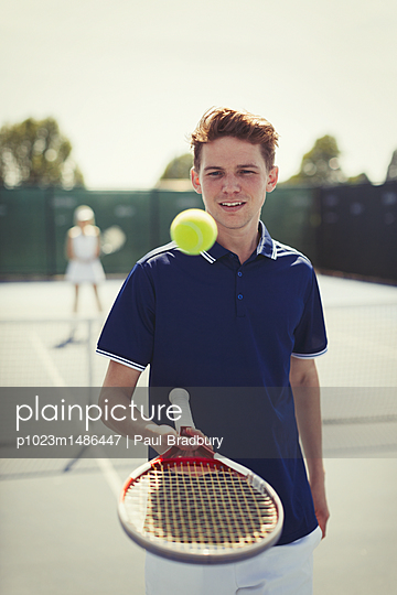 Young male tennis player bouncing tennis ball on tennis racket on tennis court