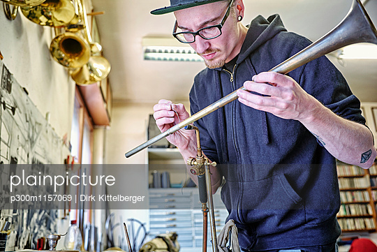 Instrument maker making trumpet in workshop - p300m1157069 by Dirk Kittelberger