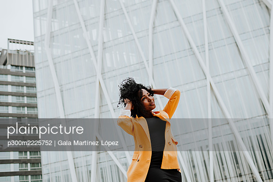 Businesswoman with hand in hair standing against building - p300m2225752 by Gala Martínez López
