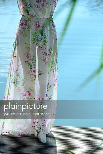 Woman in flower dress on wooden pier - p427m2210852 by Ralf Mohr