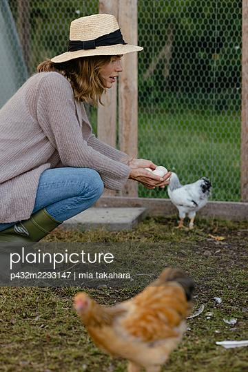 Junge Frau mit Eiern in der Hand - p432m2293147 von mia takahara