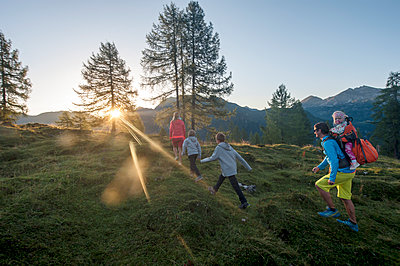 Family hiking in alpine meadow at sunset - p300m1587174 by Hans Huber
