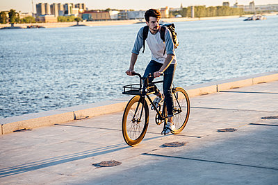 Young man with backpack riding bike on waterfront promenade at the riverside - p300m2059471 by Vasily Pindyurin