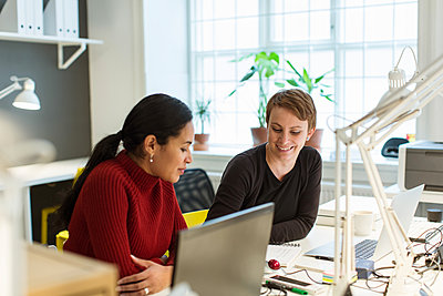 Smiling multi-ethnic female professionals working at illuminated desk in creative office - p426m1588285 by Kentaroo Tryman