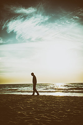 Man walking on the beach at sunset  - p794m1088245 by Mohamad Itani