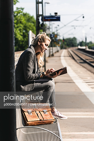 Young woman sitting at train station, using digital tablet - p300m2004007 von Uwe Umstätter
