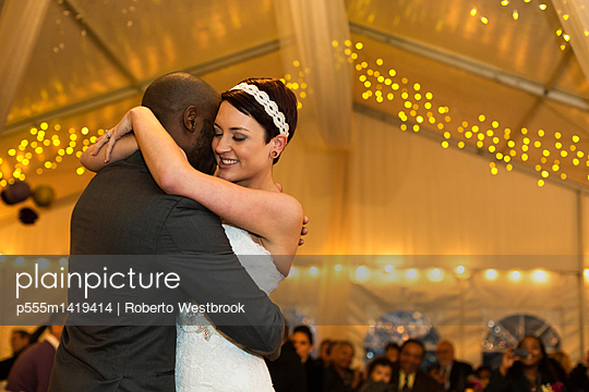 Newlywed couple dancing at reception - p555m1419414 by Roberto Westbrook