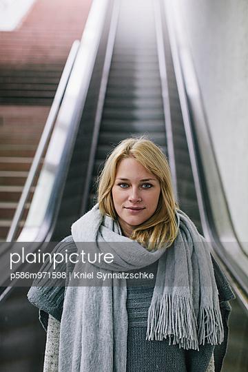 Junge Frau mit Schal auf einer Rolltreppe - p586m971598 von Kniel Synnatzschke