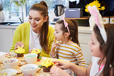 Mother with daughters decorating Easter cookies and muffins in kitchen - p300m1567648 by gpointstudio