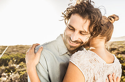 Happy young couple hugging at the coast in summer - p300m2167509 by Floco Images