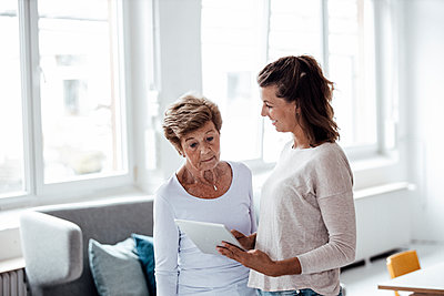 Surprised senior woman looking at digital tablet held by granddaughter at home - p300m2276852 by Gustafsson