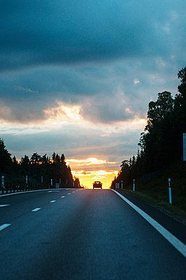 Sweden, Vastra Gotaland, Car on road at sunset - p352m1126440f by Daniel Högberg