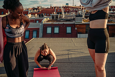 Smiling female folding exercise mat while friends wearing clothes after yoga on rooftop during sunrise - p426m2233626 by Maskot
