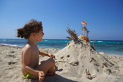 Girl building sandcastle on beach - p42916781f by Leila Mendez