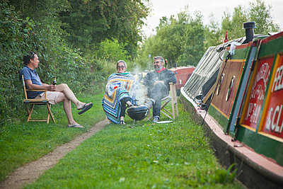 Holidaymakers Having Barbeque at Riverbank - p669m1101780 by Jutta Klee photography