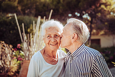 Greece, Senior man kissing his wife, portrait - p713m2283579 by Florian Kresse