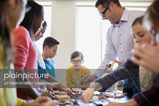 Students and teacher assembling circuit electronics at table - p1192m1019851f by Hero Images