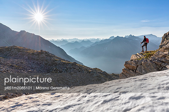 Hiker looking to the valley from the Peterskopfl, Ginzling, Zillertal, Tyrol, Austria (MR) - p651m2085101 by Moreno Geremetta