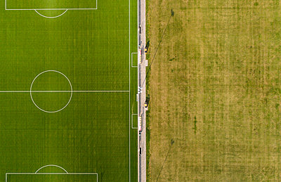 Football ground beside fields, drone photography - p1132m2215549 by Mischa Keijser